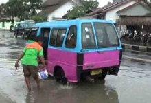 Photo of Lucu, Supir Angkot Ini Cuci Mobil di Genangan Banjir